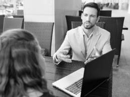 Couple negotiating at table with laptop